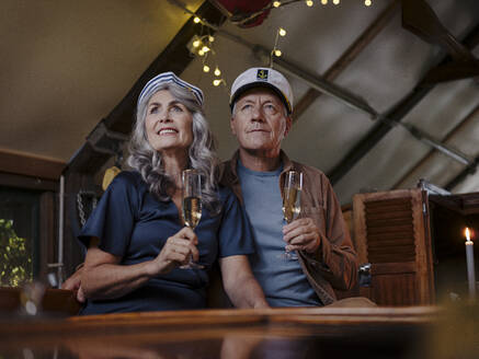 Senior couple having a candlelight dinner on a boat in boathouse - GUSF03023