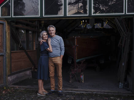 Senior couple standing in front of boathouse - GUSF03032