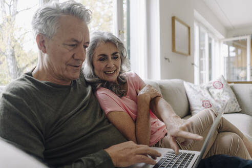Happy senior couple with laptop relaxing on couch at home - GUSF03038