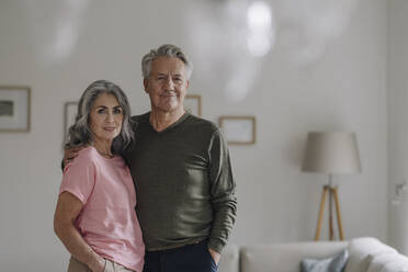 Portrait of confident senior couple standing in living room at home - GUSF03050