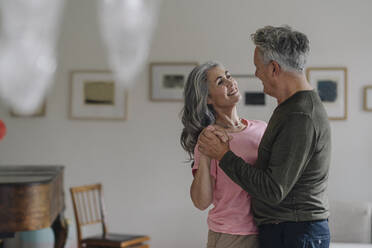 Happy senior couple dancing in living room at home - GUSF03053