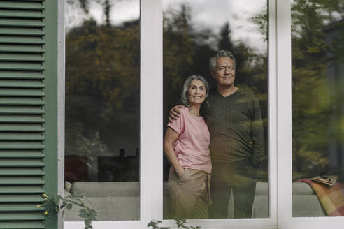 Senior couple behind windowpane of their home looking out - GUSF03062
