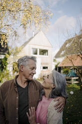 Happy senior couple in garden of their home in autumn - GUSF03068