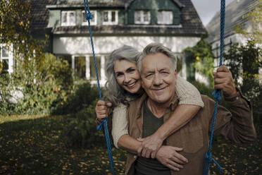 Portrait of a happy woman embracing senior man on a swing in garden - GUSF03071