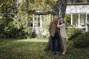 Senior couple in garden of their home in autumn - GUSF03074