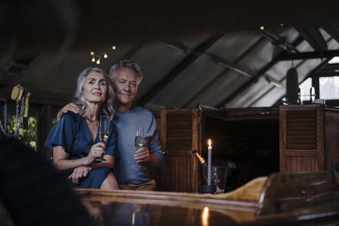 Portrait of senior couple having a candlelight dinner on a boat in boathouse - GUSF03080