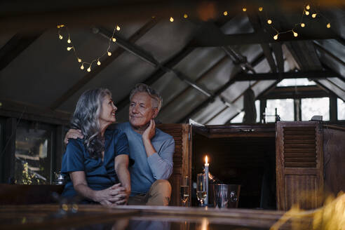 Senior couple having a candlelight dinner on a boat in boathouse - GUSF03083