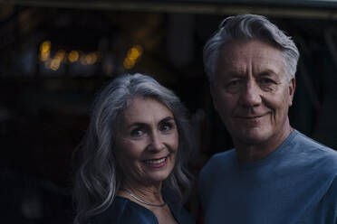 Portrait of a smiling senior couple outdoors at night - GUSF03095