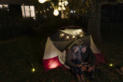 Senior couple with tablet camping in garden of their home at night - GUSF03098