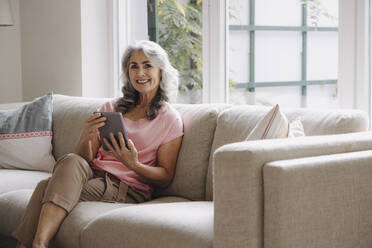 Portrait of smiling mature woman with tablet sitting on couch at home - GUSF03107