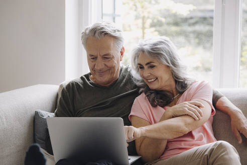 Happy senior couple with laptop relaxing on couch at home - GUSF03110