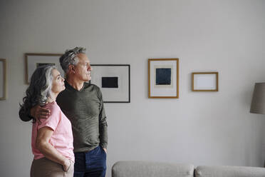 Senior couple standing in living room at home - GUSF03119