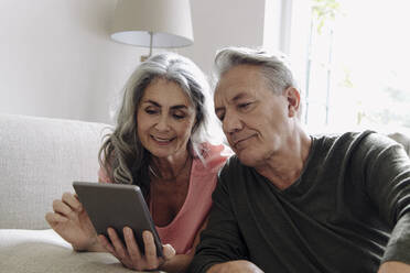 Happy senior couple relaxing on couch at home using tablet - GUSF03122