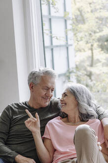 Happy senior couple relaxing on couch at home - GUSF03125