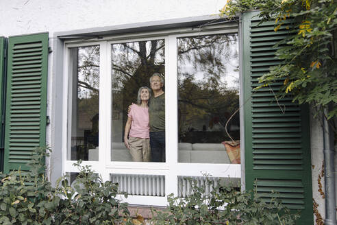 Senior couple behind windowpane of their home looking out - GUSF03128