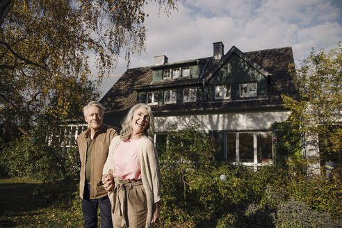 Happy senior couple in garden of their home in autumn - GUSF03131