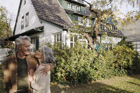 Senior couple in garden of their home in autumn - GUSF03134
