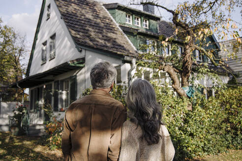 Rear view of senior couple in garden of their home in autumn - GUSF03137