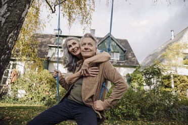 Happy woman embracing senior man on a swing in garden - GUSF03143