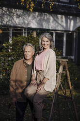 Senior couple with a ladder in garden of their home - GUSF03146