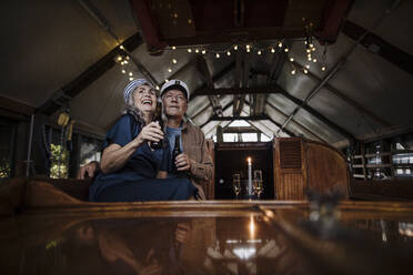 Happy senior couple having a drink on a boat in boathouse - GUSF03152