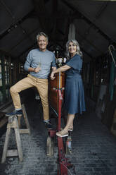 Senior couple in a boathouse with glass of champagne - GUSF03155