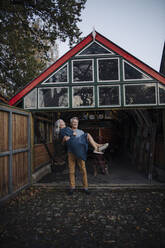 Senior man carrying his wife in front of boathouse - GUSF03158