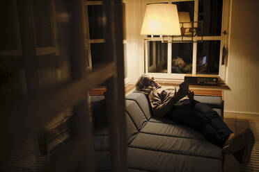 Mature woman using tablet on couch at home in the dark - GUSF03161