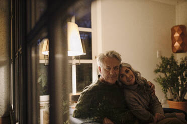 Portrait of senior couple relaxing on couch at home at night - GUSF03164