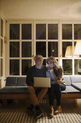 Senior couple using laptop on couch at home at night - GUSF03167