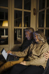 Senior couple using laptop on couch at home at night - GUSF03170