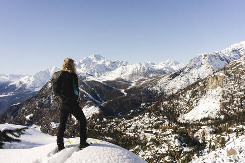 Woman stanging with snowshoes on viewpoint, Valmalenco, Italy - MRAF00465