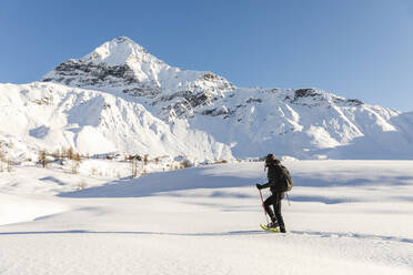 Woman walking with snowshoes in fresh snow in the mountains, Valmalenco, Italy - MRAF00477