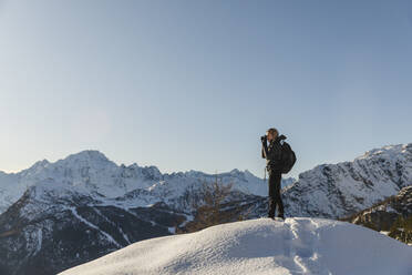 Woman taking a photo of winter mountain landscape, Valmalenco, Italy - MRAF00480