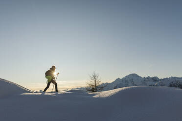 Woman walking with snowshoes in fresh snow in the mountains at sunset, Valmalenco, Italy - MRAF00483