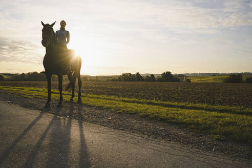 Woman on horse in the countryside at sunset - JOSF04123