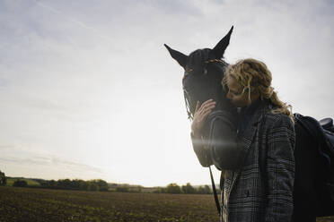 Affectionate young woman with horse on a field in the countryside at sunset - JOSF04135