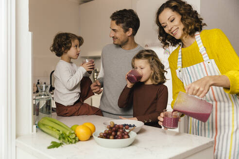Mother preparing a smoothie for her family in kitchen - MFF04939