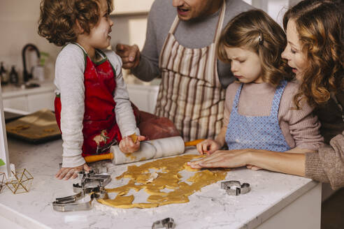 Family preparing Christmas cookies in kitchen - MFF04951