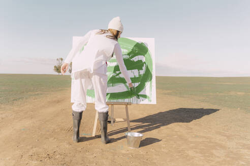 Young woman on dry field, painting canvas with green paint - ERRF02343