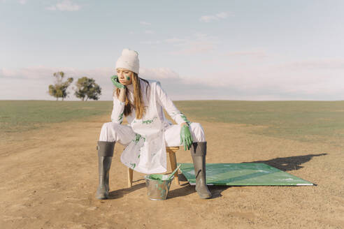 Young woman sitting on stool with green painting on dry field - ERRF02379