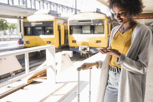 Smiling young woman with earphones and smartphone at platform - UUF19739