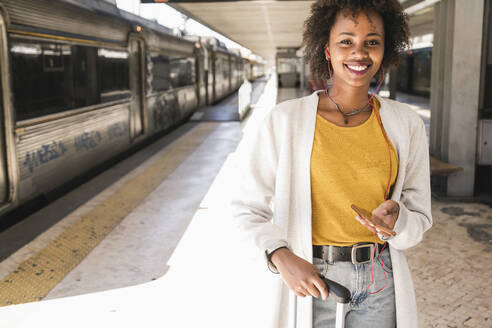 Portrait of smiling young woman with earphones and smartphone at platform - UUF19742