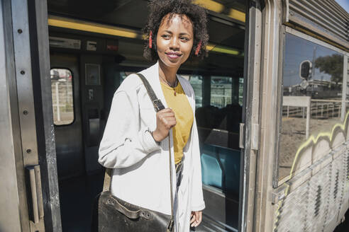 Smiling young woman standing in train door - UUF19763