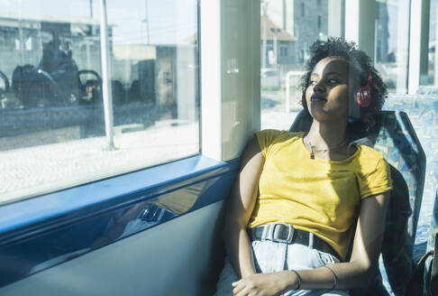 Young woman with headphones relaxing in a train - UUF19787