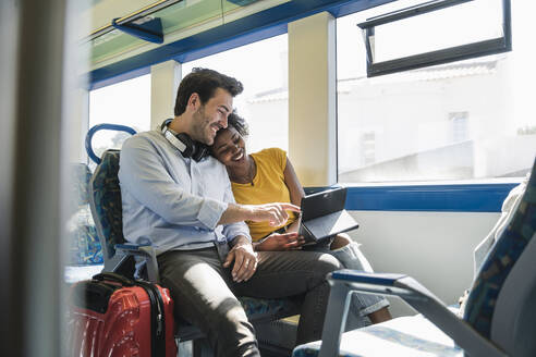 Happy young couple using tablet in a train - UUF19793