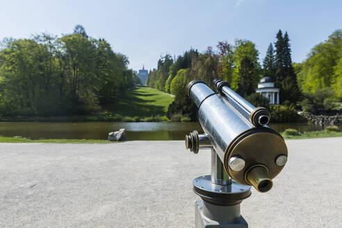 Germany, Hesse, Kassel, Coin operated binoculars in front of pond in Bergpark Wilhelmshohe - RUNF03501