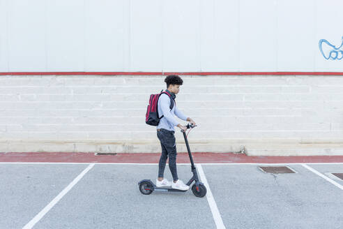 Young man riding e-scooter on parking deck - JPTF00378