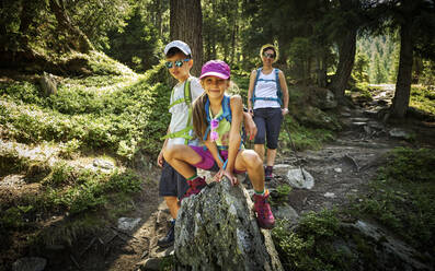 Portrait of mother with two children hiking in alpine scenery, Passeier Valley, South Tyrol, Italy - DIKF00321