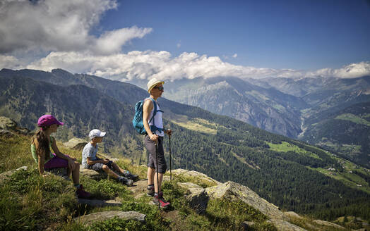 Mother with two children having a break from hiking in alpine scenery, Passeier Valley, South Tyrol, Italy - DIKF00327